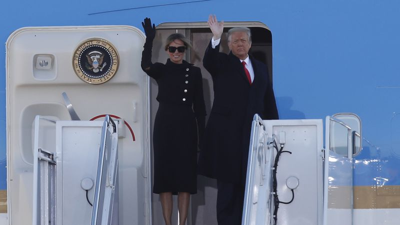 President Donald Trump and first lady Melania Trump wave to a crowd as they board Air Force One...