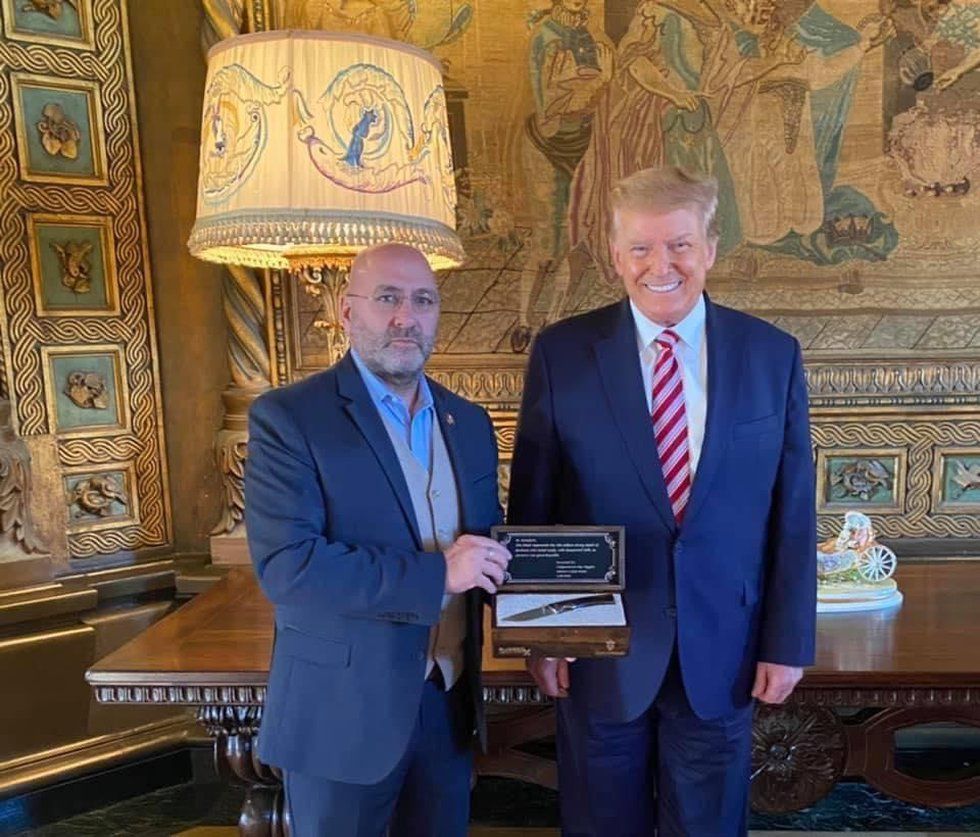 Congressman Clay Higgins of Louisiana presents the knife to former President Donald Trump.
