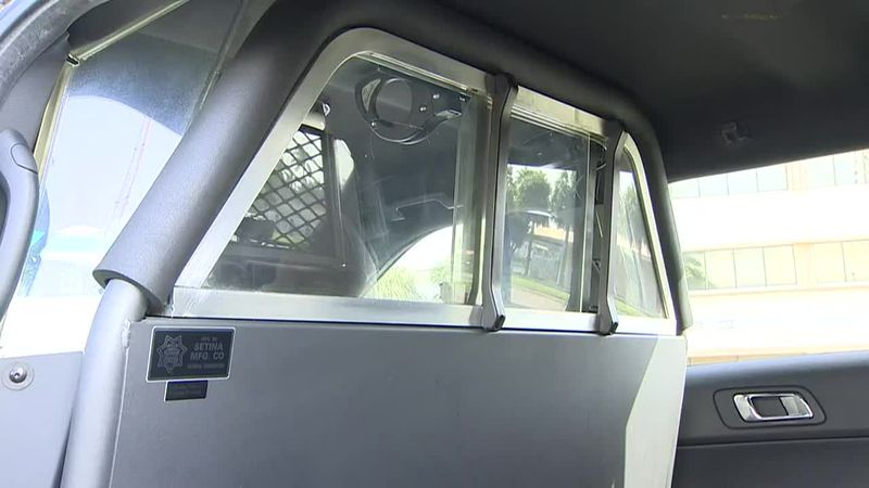 The view from the back seat of a South Florida police department vehicle is shown. A Miami...