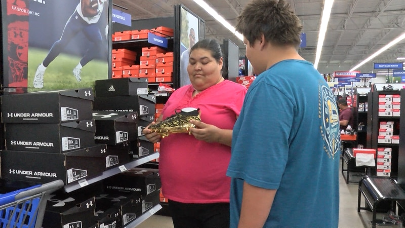 Krista Ramon and her son check out a pair of cleats at Academy Sports and Outdoors.