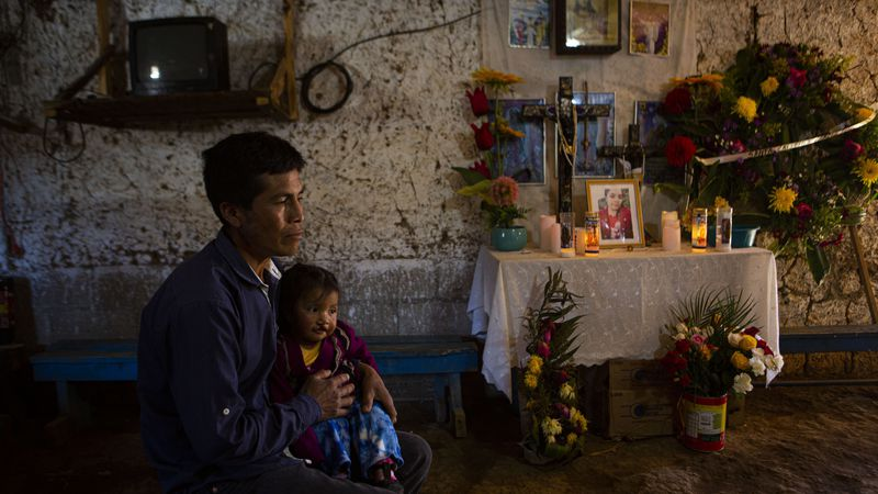 Ricardo Garcia and daughter Angela sit next to an altar adorned with photographs of his older...