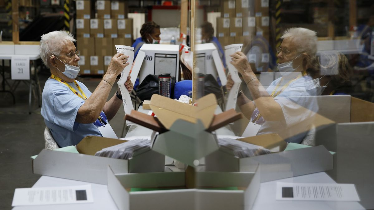 FILE - In this June 9, 2020, file photo, election workers process mail-in ballots during a...