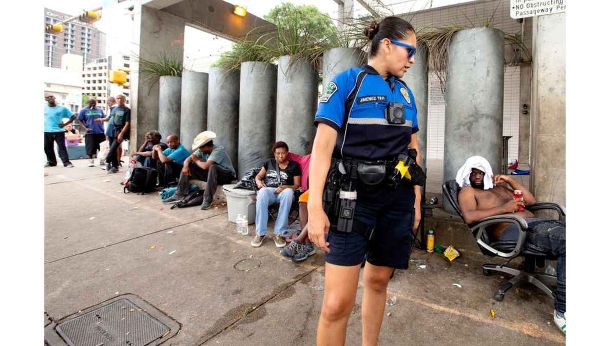 An Austin police officer speaks to people gathered on sidewalk in front of the Austin Resource Center for the Homeless, or ARCH, in downtown Austin in August. (Photo: Marjorie Kamys Cotera for The Texas Tribune)