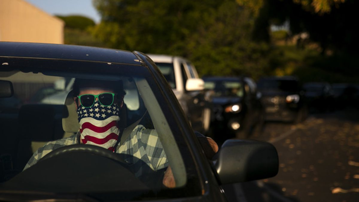Charles McNulty wears a face covering while waiting in his car to purchase a movie ticket at Mission Tiki drive-in movie theater in Montclair, Calif., Thursday, May 28, 2020. (AP Photo/Jae C. Hong)