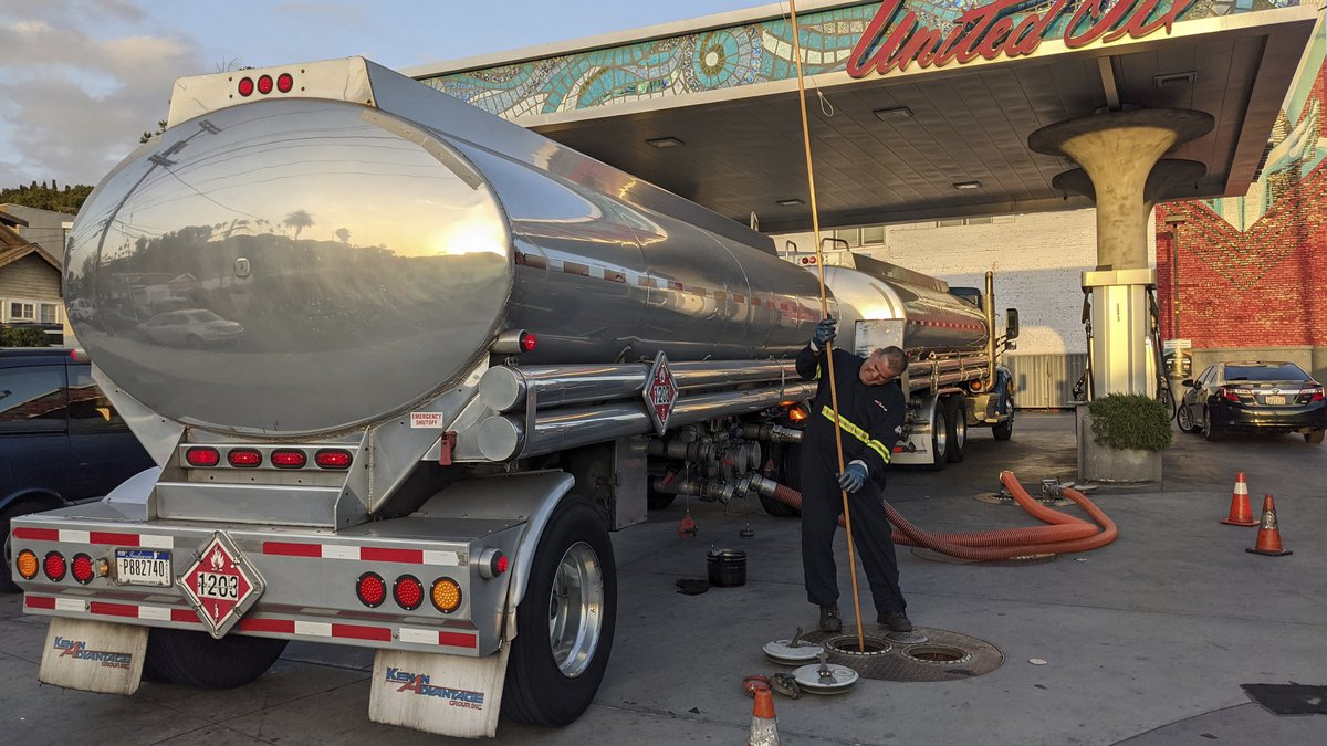 In this May 20, 2021 photo, a fuel truck driver checks the gasoline tank level at a United Oil...