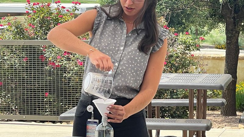 Laura Bohorquez, completions engineer at XTO Energy shows students how to make 'elephant...
