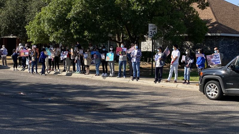 Protesters lined the sidewalk outside of Bob Fu's home in Midland.
