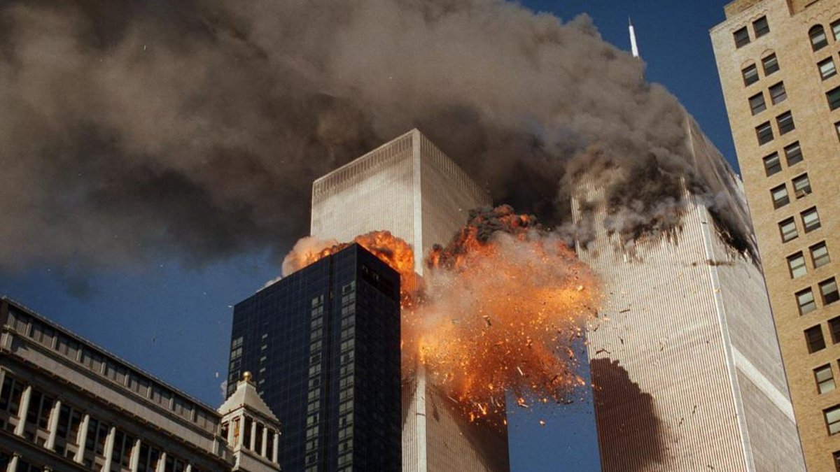 Smoke billows from one of the towers of the World Trade Center as flames and debris explode...