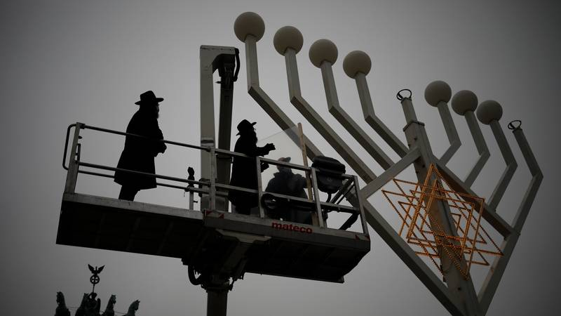 Rabbi Yehuda Teichtal, left, and Rabbi Segal Shmoel, second from left, inspect a giant Hanukkah...