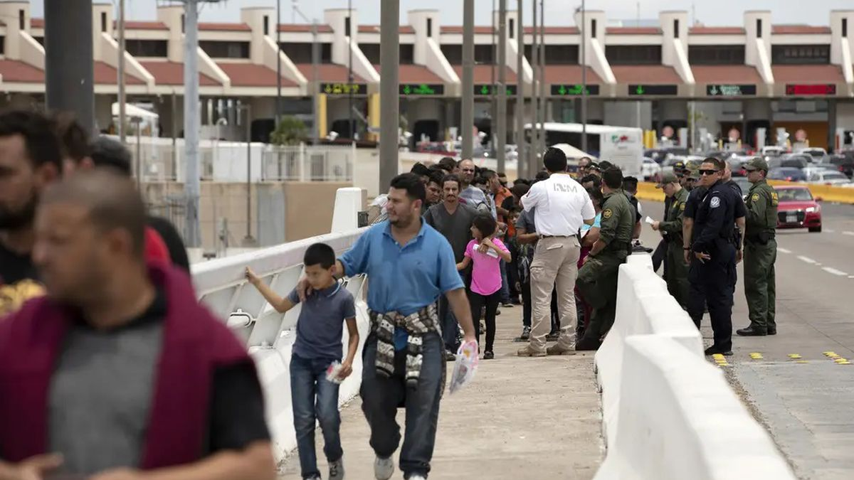 A group of migrants walk across Internation Bridge Two into Mexico from the United States. The...