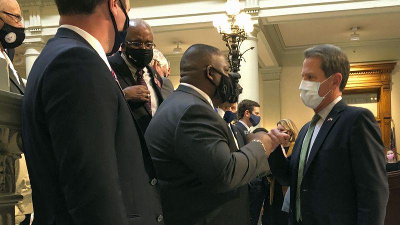 Georgia Gov. Brian Kemp, right, bumps fists with Democratic state Rep. Carl Gilliard of Garden...