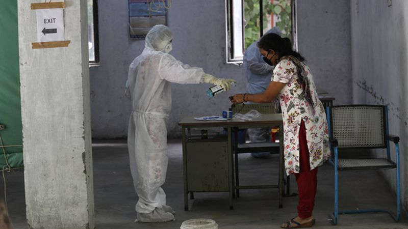 A health worker gives hand sanitizer to a woman after taking her sample for the COVID-19 rapid...
