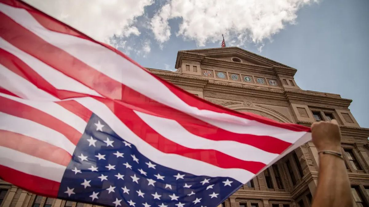 Brendan Cavanagh waves an American flag while participating in a rally opposing Senate Bill 7...