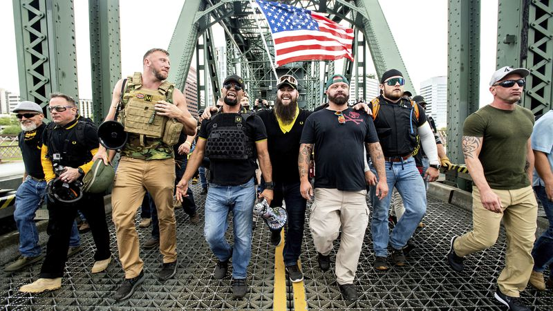 Members of the Proud Boys, including organizer Joe Biggs, third from right, march across the...