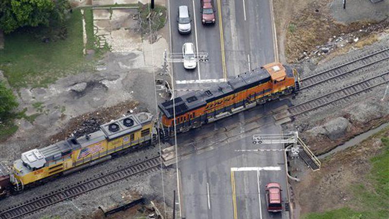 Burlington Northern Santa Fe locomotives make their by a rail road crossing Tuesday, May 21,...