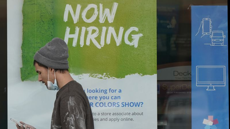"""A man walks past a """"Now Hiring"""" sign on a window at a Sherwin-Williams store, Friday, Feb. 26,..."""