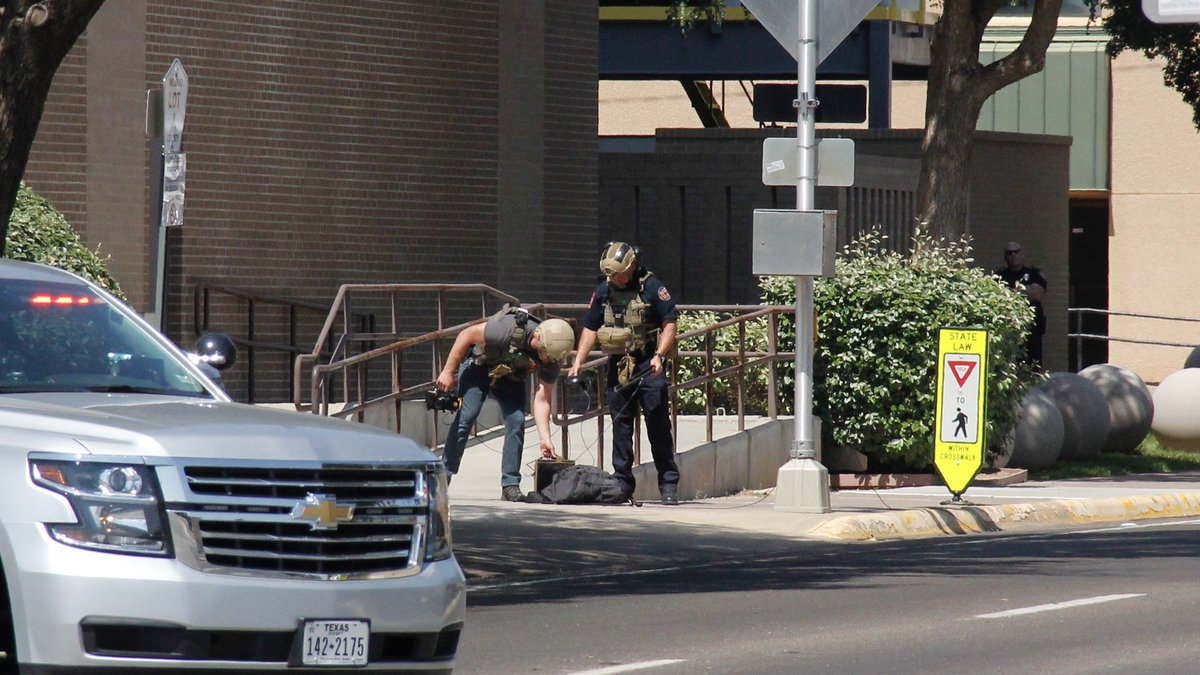 Members of the bomb squad inspect the suspicous bag left outside of the Midland County...