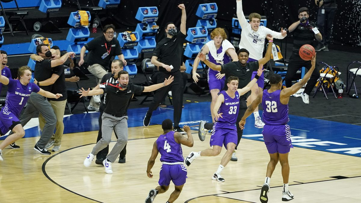 Abilene Christian players celebrate their 53-52 upset win over Texas in a college basketball...