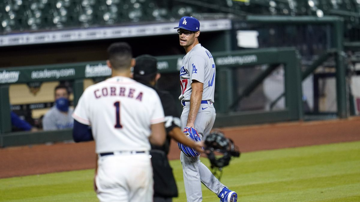Los Angeles Dodgers relief pitcher Joe Kelly (17) talks toward Houston Astros' Carlos Correa (1) after the sixth inning of a baseball game Tuesday, July 28, 2020, in Houston. Kelly received an eight-game suspension for his actions after he threw a pitch in the area of the head of Houston Astros' Alex Bregman and later taunted Correa, which led to the benches clearing. (AP Photo/David J. Phillip)