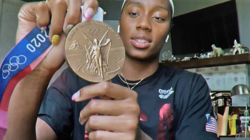 Natalie Hinds holds up her Olympic bronze medal