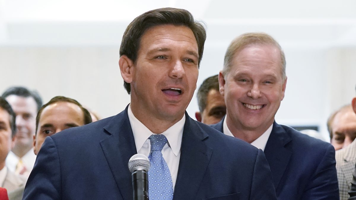 FILE - In this April 30, 2021, file photo surrounded by lawmakers, Florida Gov.Ron DeSantis...